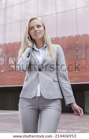Beautiful young businesswoman conversing on cell phone while standing against office building - stock photo