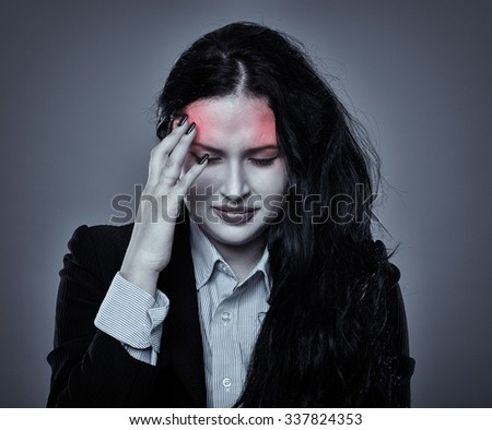 Beautiful young businesswoman having a strong migraine, over gray background - stock photo