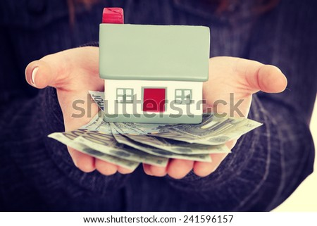 Beautiful young businesswoman holding euros bills and house model over white - real estate loan concept - stock photo