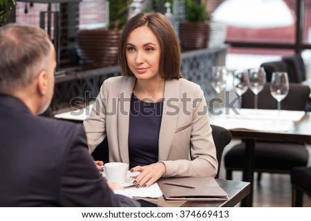 Beautiful young businesswoman is drinking coffee with her business partner in cafe. They are sitting at the table. The lady is looking at mature man and gently smiling - stock photo