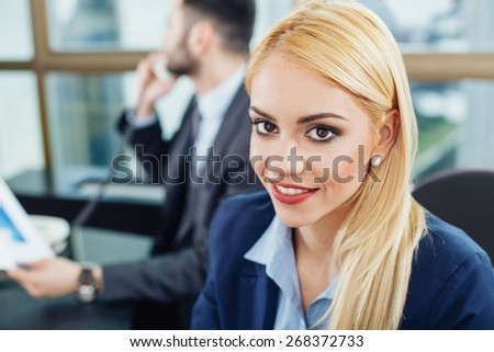 Beautiful young businesswoman posing with a smile in office with a man out of focus in the background - stock photo