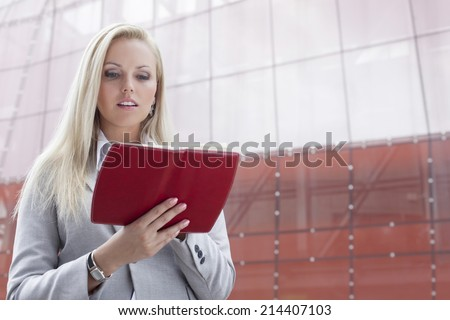 Beautiful young businesswoman reading notes in organizer while standing against office building - stock photo