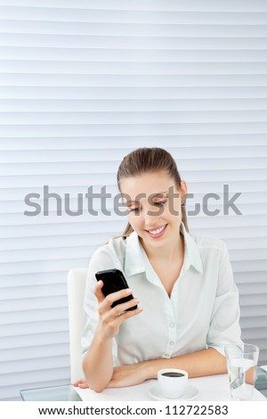 Beautiful young businesswoman reading text message on cell phone while sitting at table with tea and glass of water - stock photo