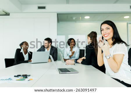 Beautiful young businesswoman receiving good news on the phone  - stock photo