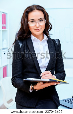 Beautiful young businesswoman smiling at the camera. Business, finance. - stock photo