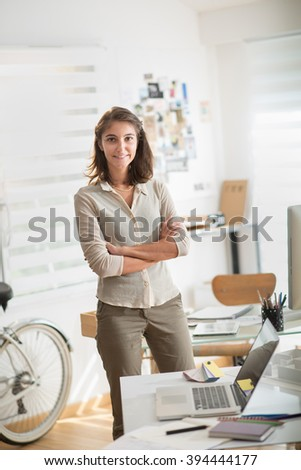 Beautiful young businesswoman standing at her desk and looking at camera, the office is modern and bright. Shot with flare - stock photo
