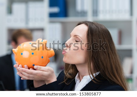 Beautiful young businesswoman standing in her office kissing her piggy bank which she is holding cupped in her hands - stock photo