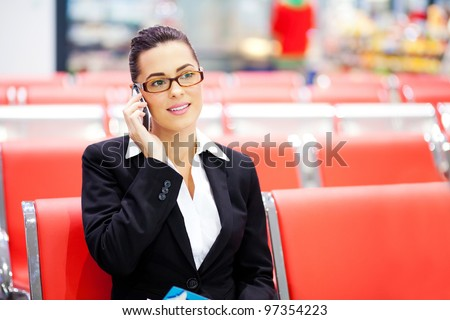 beautiful young businesswoman talking on cell phone at airport - stock photo