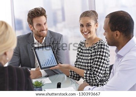 Beautiful young businesswoman using tablet computer at a business meeting, smiling happy. - stock photo