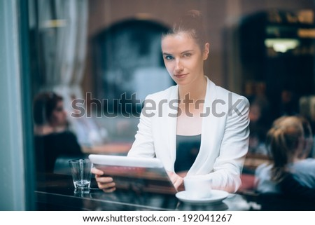 Beautiful young businesswoman using tablet computer in coffee shop - stock photo