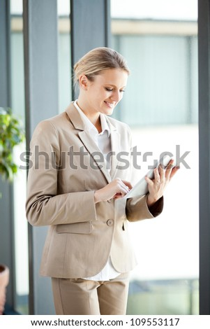 beautiful young businesswoman using tablet computer in office - stock photo