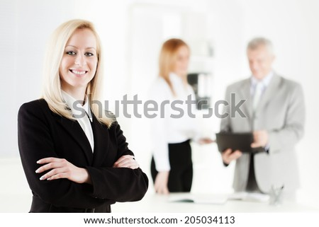 Beautiful young businesswoman with Arms Crossed in the office. Looking at camera. Selective Focus. - stock photo