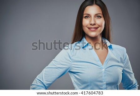 Beautiful young businesswoman with hands on hips looking confident against a gray background - stock photo