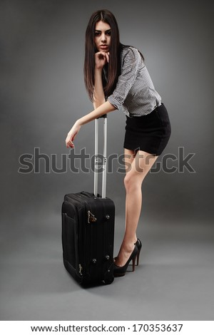 Beautiful young businesswoman with luggage over gray background, traveling concept - stock photo