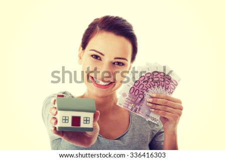 Beautiful young, casual woman holding money and house. - stock photo