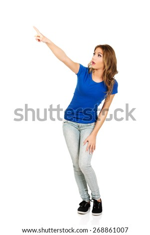Beautiful young casual woman pointing up. - stock photo