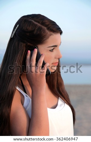 Beautiful young caucasian teenage girl with long dark hair on her cell phone. - stock photo