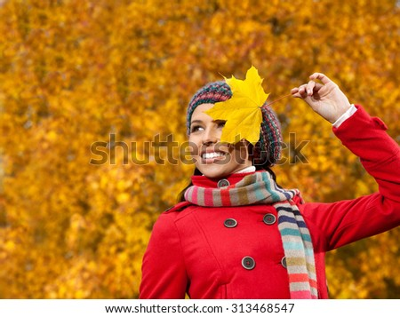 beautiful young caucasian woman in warm red colorful clothing  on yellow maple leaves outdoors smiling happy  - stock photo