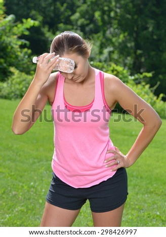 Beautiful young Caucasian woman in workout gear pauses from outdoor work-out  - looking miserable as she holds a bottle of water to head to cool down - stock photo