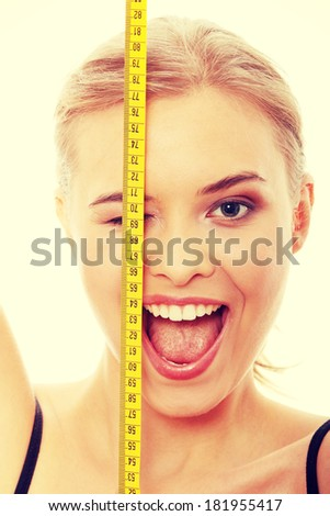 Beautiful young caucasian woman measuring her body with tape - stock photo