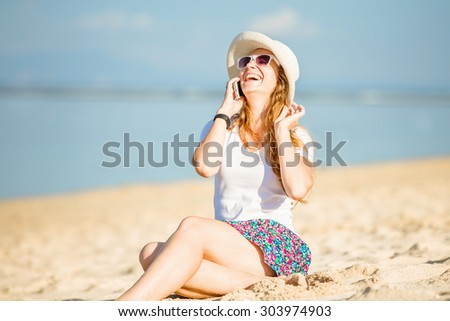 Beautiful young caucasian woman on the beach in white hat talking on mobile phone and laughing. Sunny day on summer vacation - stock photo