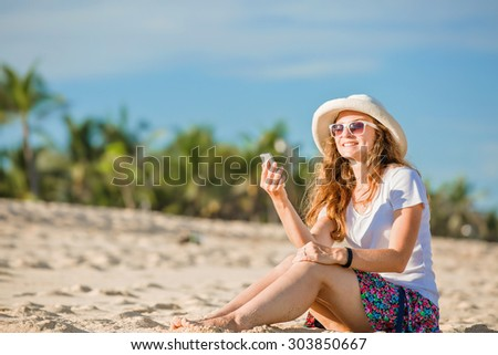 Beautiful young caucasian woman on the beach in white hat  with mobile phone. Sunny day on summer vacation - stock photo