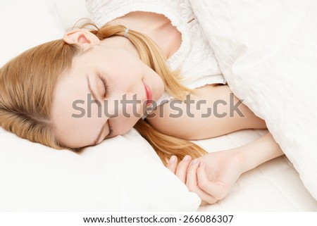 Beautiful young caucasian woman sleeping on the bed - stock photo