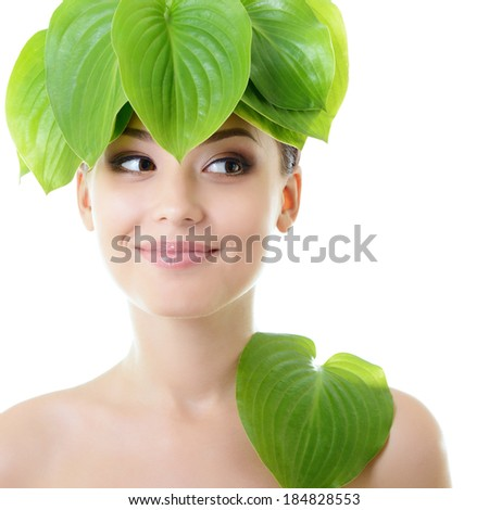 Beautiful young cheerful woman looking left at copyspace. Girl with green leaves near her face. Care of nature concept, over white background. - stock photo