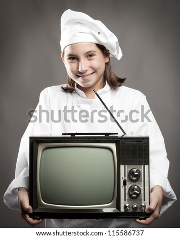 beautiful young chef  holding television on gray background - stock photo