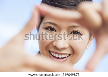 Beautiful young Chinese Asian woman girl smiling, making and looking through a finger frame  - stock photo