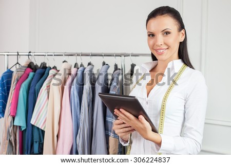 Beautiful young clothes designer is using a laptop for her work. She is looking at the camera and smiling. The woman has a tape-line over her neck - stock photo
