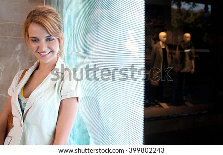 Beautiful young consumer woman leaning on a digital led lights screen in a shopping mall looking at camera, smiling indoors. Joyful portrait of attractive woman by shop window, lifestyle. - stock photo