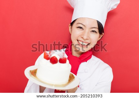 beautiful young cook woman holding a whole cake against red background - stock photo