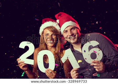 Beautiful, young couple celebrating New Year's Eve, holding cardboard numbers 2016 - stock photo