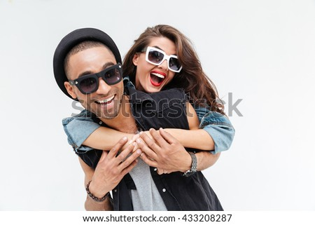 Beautiful young couple embracing and laughing over white background - stock photo