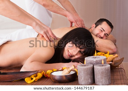Beautiful Young Couple Enjoying Massage In Spa Centre - stock photo