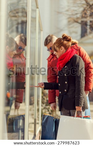 Beautiful young couple going shopping and carrying shopping bags. - stock photo