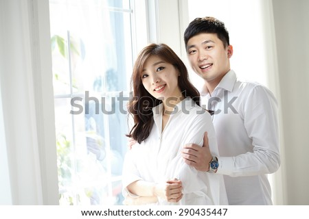 beautiful young couple having a pleasant conversation while looking out a window in a bright room - stock photo