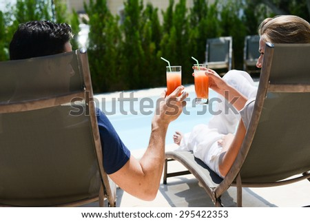 beautiful young couple having drink in deck chairs by the pool in holiday resort - stock photo