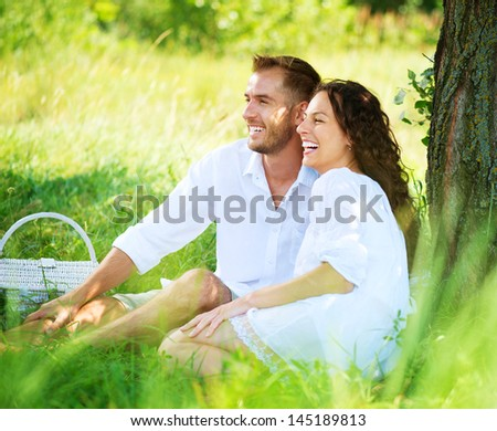Beautiful Young Couple Having Picnic in Countryside. Happy Family Outdoor. Smiling Man and Woman relaxing in Park. Relationships - stock photo
