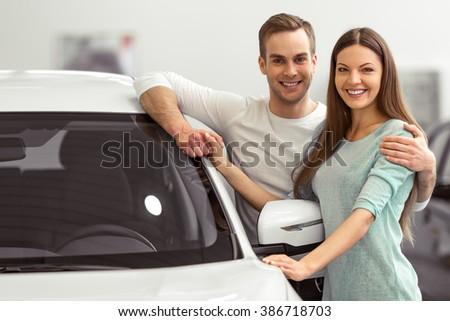 Beautiful young couple in casual clothes is smiling and looking at camera while leaning on their new car in a motor show - stock photo