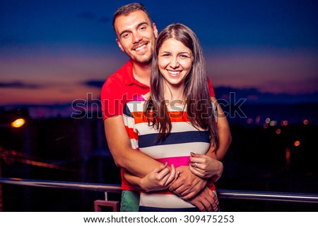 Beautiful young couple in love after sunset - stock photo