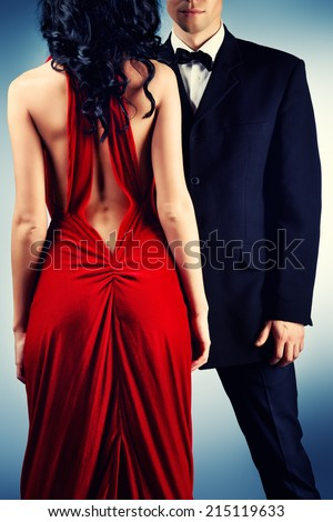 Beautiful young couple in love in evening dresses posing at studio. Fashion. - stock photo