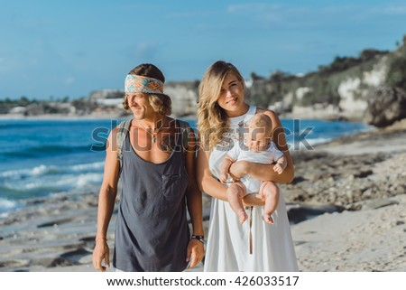 beautiful young couple in love with a child on the beach. couple with a kid in the sunset on the ocean. happy family with a baby.young family hippie hipsters.young mother with long hair holds a child. - stock photo