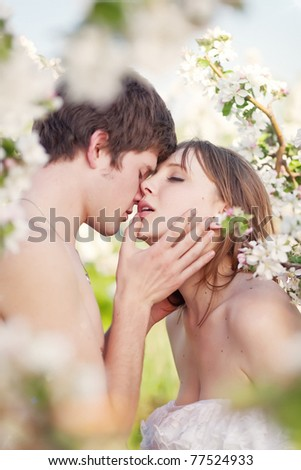 beautiful young couple kissing in the flowering gardens - stock photo