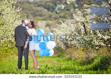 beautiful young couple kissing in the flowering trees - stock photo