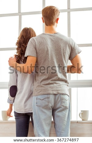 Beautiful young couple look in the window, standing next to a cup, at home - stock photo