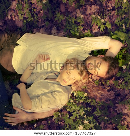 beautiful young couple lying on the spring meadow - stock photo