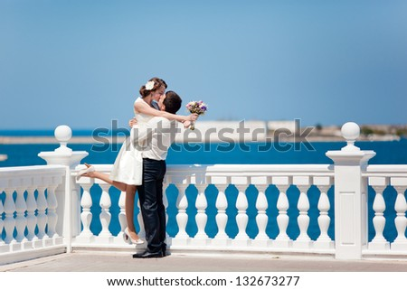 beautiful young couple man and woman hugging and kissing outdoors at the sea in a sunny day - stock photo