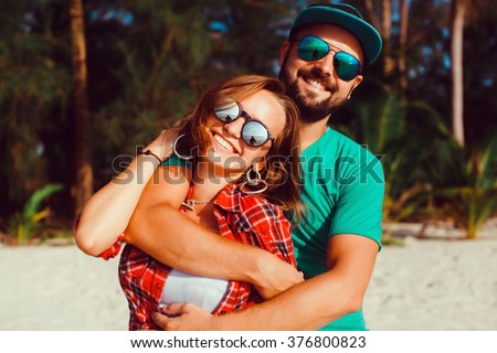 beautiful young couple of hipsters in trendy clothes, the bearded guy, t-shirt, shorts, blue baseball cap, wearing sunglasses, smiling, happy lovers,at the beach near the sea outdoor portrait,close up - stock photo